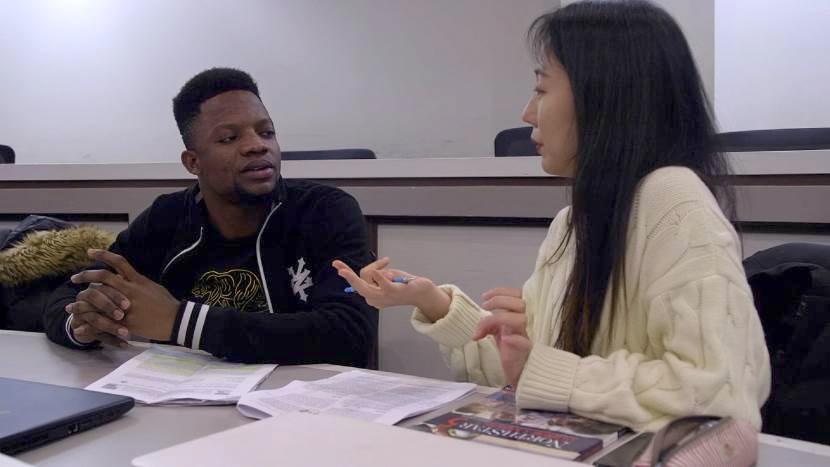 两名ELI学生在桌子前交谈