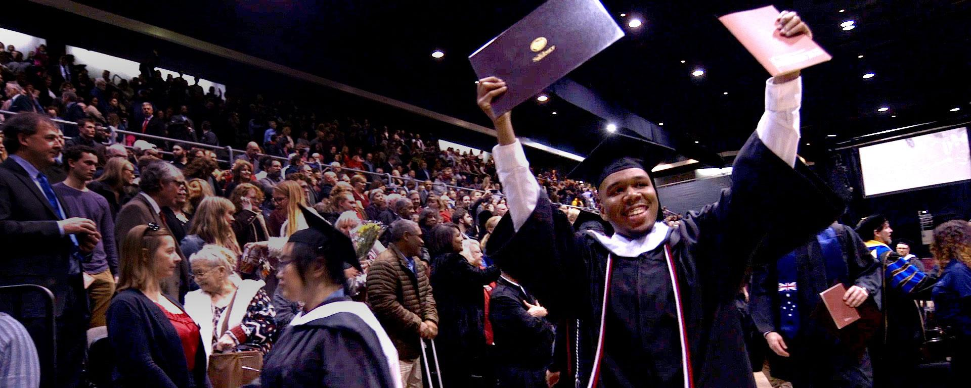 Student holding up diploma at commencement ceremony