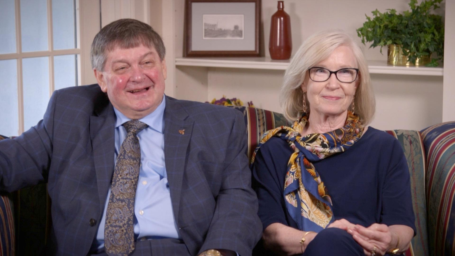 Glenda Chatham and Robert G. Clarke sitting on a couch looking at camera.