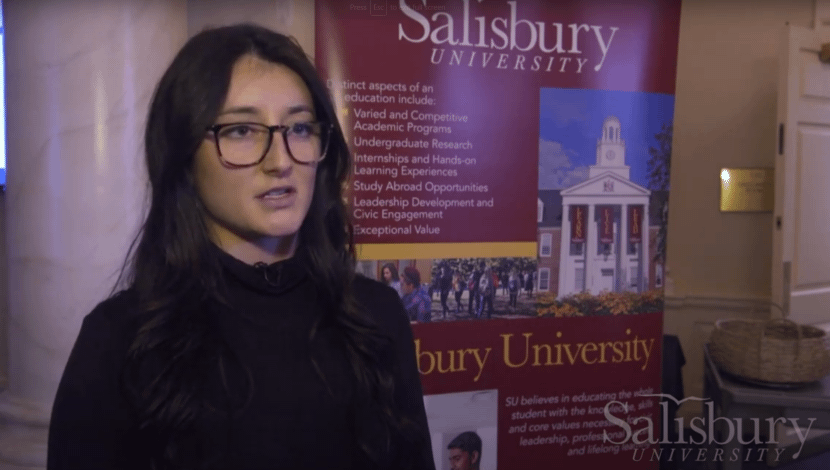 Student speaks at posters on the bay