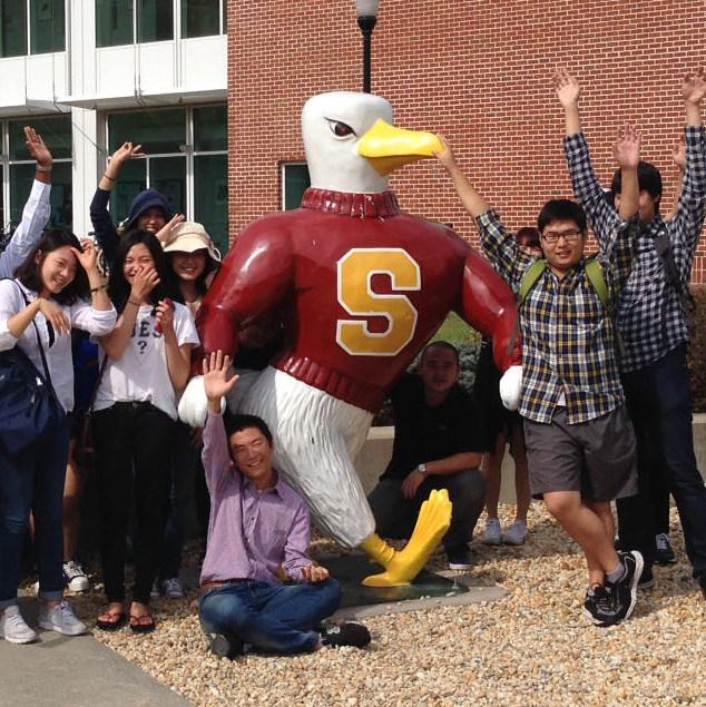 students posing around Sammy the Seagull outside Henson