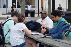 Students sitting outside at table